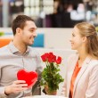 Happy couple with present and flowers in mall — Stock Photo #59669469