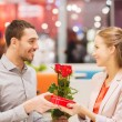 Happy couple with present and flowers in mall — Stock Photo #59669481