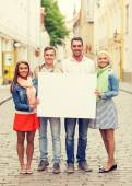Group of smiling friends with blank white board — Stock Photo