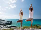 Couple making yoga exercises on beach from back — Stock Photo