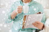 Close up of man with magazine drinking from cup — Stock Photo