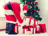 Man in costume of santa claus with presents — Stock Photo