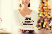 Close up of woman showing gingerbread house — Stock Photo