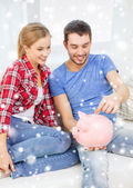 Smiling couple with piggybank sitting on sofa — Stok fotoğraf