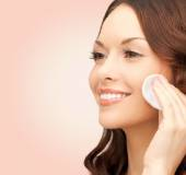 Smiling woman cleaning face skin with cotton pad — Stock Photo