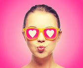 Girl in pink sunglasses blowing kiss — Stock fotografie