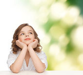 Beautiful girl sitting at table and looking up — Stock Photo
