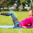 Smiling woman doing exercises on mat outdoors — Stock Photo #60088055