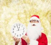 Man in costume of santa claus with clock — Stockfoto