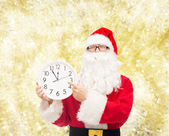 Man in costume of santa claus with clock — Stock fotografie