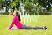 Smiling woman stretching back on mat outdoors — Foto de Stock