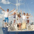 Smiling friends sitting on yacht deck and greeting — Stock Photo #60138561