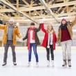 Happy friends waving hands on skating rink — Stock Photo #60138921