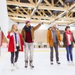 Happy friends pointing finger on skating rink — Stock Photo #60138967