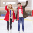 Happy girls friends waving hands on skating rink — 图库照片 #60138985