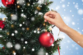 Close up of hand with christmas tree decoration — Stock Photo