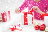Close up of woman decorating christmas presents — Foto de Stock