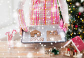 Closeup of woman with gingerbread house on pan — Stock Photo
