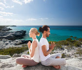 Smiling couple making yoga exercises outdoors — Stock Photo