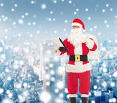 Man in costume of santa claus with notepad and bag — Stockfoto