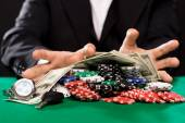 Poker player with chips and money at casino table — Stock fotografie