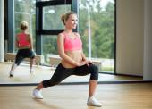 Smiling woman stretching leg in gym — Stock Photo