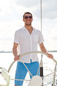 Young man in sunglasses steering wheel on yacht — Foto Stock