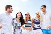 Smiling friends in sunglasses talking on beach — Stockfoto