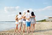 Smiling friends hugging and walking on beach — Stock Photo