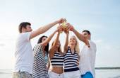 Sorrindo amigos tilintar de garrafas na praia — Fotografia Stock