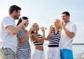ドリンク ボトルにビーチで友達に笑顔 — ストック写真