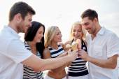 Smiling friends eating ice cream on beach — Стоковое фото
