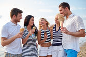 Friends eating ice cream and talking on beach — Stok fotoğraf