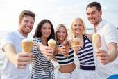 Smiling friends eating ice cream on beach — Stok fotoğraf