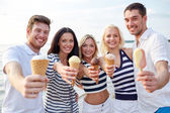 Smiling friends eating ice cream on beach — Stockfoto