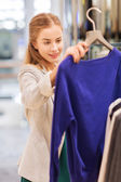 Happy young woman choosing clothes in mall — Foto de Stock