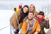 Happy friends with smartphone on skating rink — Stock Photo
