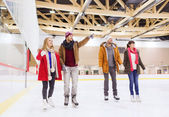 Happy friends pointing finger on skating rink — Stock Photo