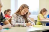 Gruppo di bambini di scuola scrivere test in aula — Foto Stock