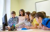 Group of kids with teacher and computer at school — Stock Photo