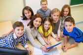 Group of kids with teacher and tablet pc at school — Stock Photo