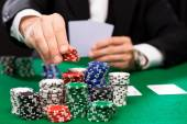 Poker player with cards and chips at casino — Stock Photo