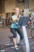 Smiling woman exercising on exercise bike in gym — Стоковое фото