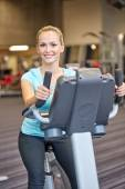 Smiling woman exercising on exercise bike in gym — Foto de Stock