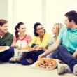 Five smiling teenagers eating pizza at home — Stock Photo #60140479