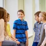 Group of smiling school kids talking in corridor — Stock Photo #60142557