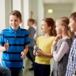 Group of school kids with soda cans in corridor — Stock Photo #60142569