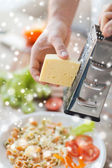 Close up of male hands with grater grating cheese — Стоковое фото