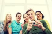 Usmívající se studenty s digitálním fotoaparátem ve škole — Stock fotografie