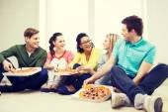 Cinco adolescentes sorridentes comer pizza em casa — Foto Stock